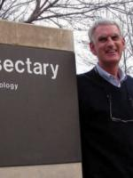 "Photo of Donald Lewis next to the building sign that says ""Insectary"""