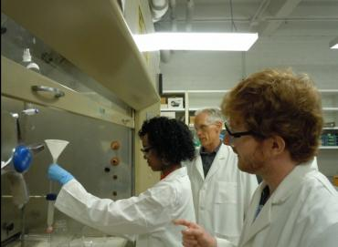 Photograph of Alayjah Muhammad, Dr. Joel Coats, and Edmund Norris working in the lab.