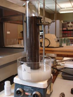 Picture of a soil column experiment. The packed soil column is placed vertically in a formulated insecticide which moves up the column through capillary action, to determine how far a pesticides will travel in soil.